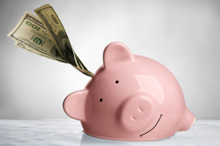 Pink piggy bank with banknote in water on light background Stock fotó