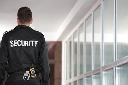 Security man standing back in corridor