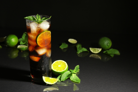 Cuba libre cocktail with mint and lime on dark background