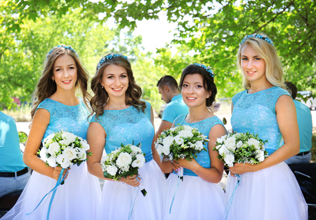 Beautiful bridesmaids with bouquets of flowers in park