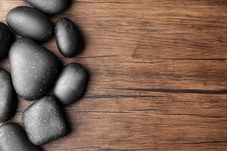 Spa stones on wooden background, top view
