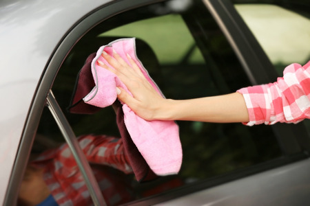 Woman wiping car with rag