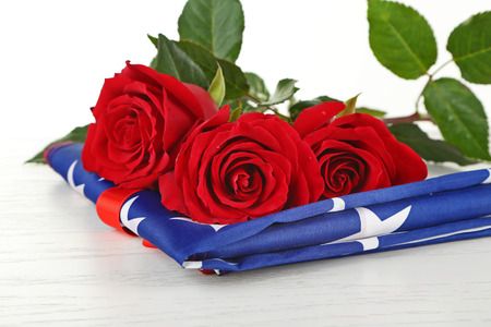 Red roses on American flag, closeup