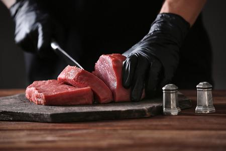 Butcher cutting pork meat on kitchen Standard-Bild