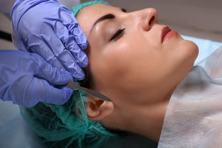 Surgeon hands with scalpel above female face