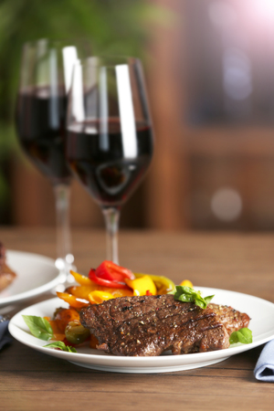 Gourmet steak with vegetables and glasses of red wine on wooden table
