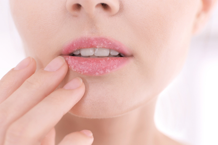 Lips of beautiful young woman covered with sugar scrub
