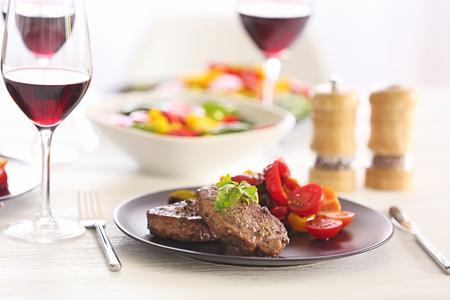 Tasty steak with fried vegetables on dinner table