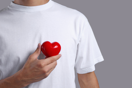 Young man with red heart on grey background Stock Photo