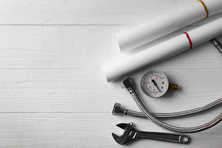 Plumber tools on white wooden background