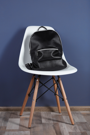 Black leather rucksack on white chair and dark background Stock Photo