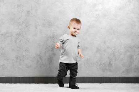 Fashionably dressed baby boy posing on a gray wall background