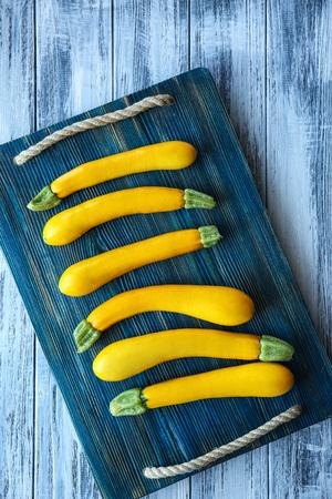 Fresh yellow zucchini on wooden cutting board Stock Photo
