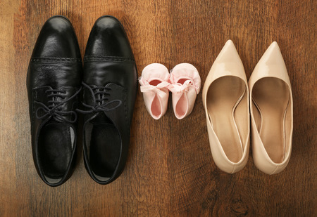 Family concept. Shoes for parents and child on wooden background