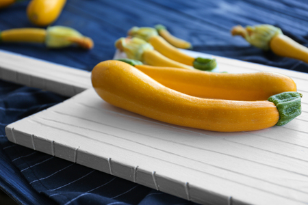 Fresh yellow zucchini on wooden cutting board Foto de archivo - 107513225