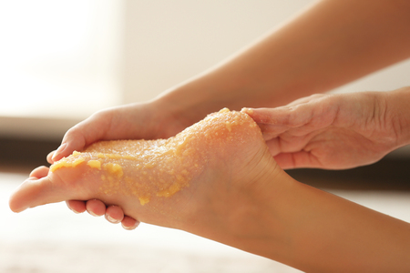 Spa concept. Hands massaging female foot with scrub Stock Photo