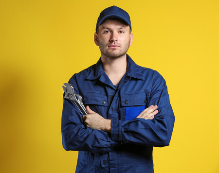 Young mechanic with crossed arms and wrench standing