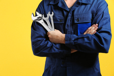 Mechanic with crossed arms and wrench standing on yellow background Stock Photo