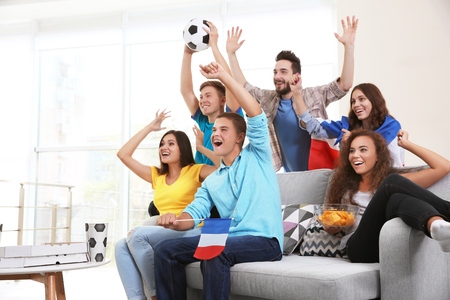 Soccer fans with France flag emotionally watching game in the room
