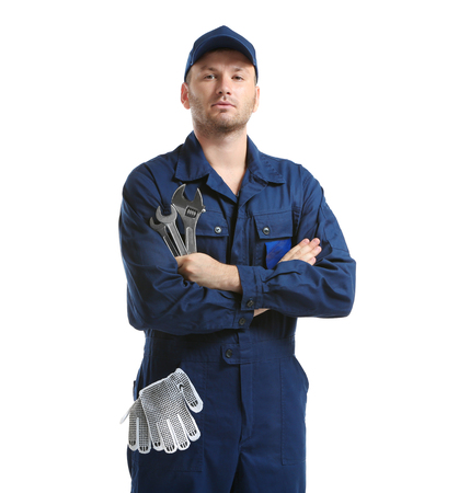 Young mechanic in uniform with a wrench and gloves in pocket