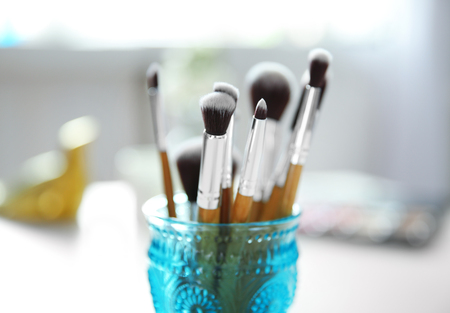 Set of makeup brushes in blue glass on blurred background