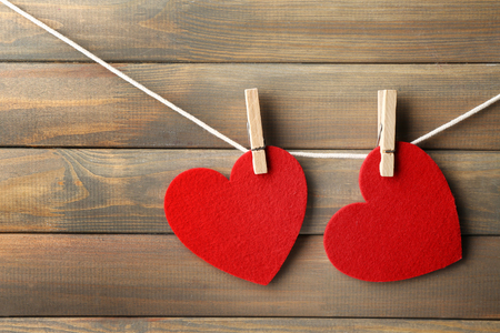 Red hearts hanging on clothespins on wooden background