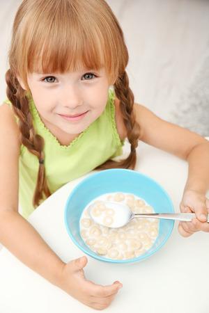 Portrait of little girl eating cornflakes with milk Reklamní fotografie