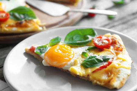 Margarita pizza with basil leaves and egg on plate closeup 版權商用圖片