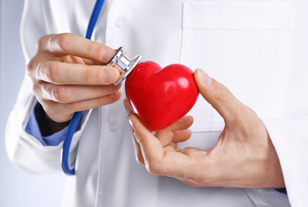 Male doctor hands attaching stethoscope to red heart, close up view