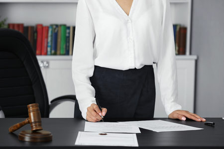 Woman signing important documents in modern office Фото со стока