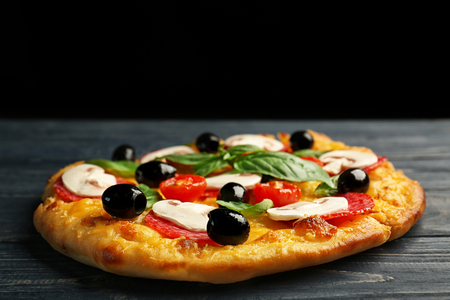 Delicious pizza with mushrooms, cherry tomatoes, olives and basil on blue wooden table and black background