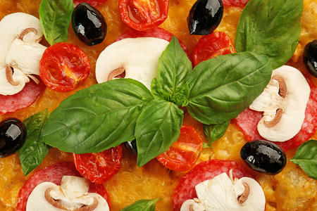 Delicious pizza with mushrooms, cherry tomatoes, olives and basil, closeup 免版税图像