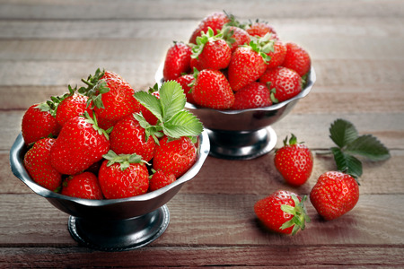 Metal bowls with fresh strawberries on wooden background