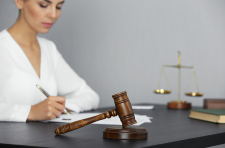Judge gavel and businesswoman sitting at table