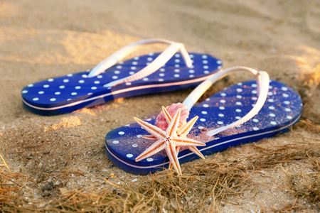 Sandals and starfish on sea sand, close up view