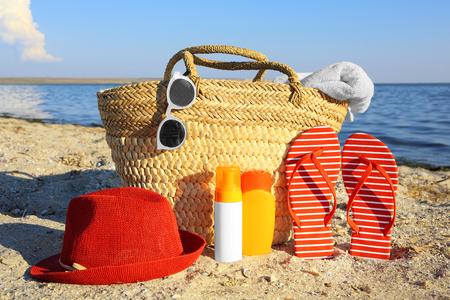 Beach bag, sandals, hat, sunscreen cream and sunglasses on sea coast 스톡 콘텐츠