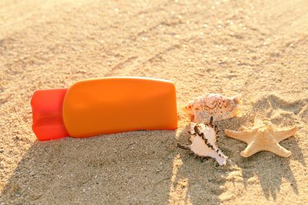 Sunscreen cream, sea shells and starfish on sand, close up view