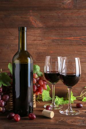 木製の背景にブドウを持つワインボトルとグラス 写真素材 - 107597761