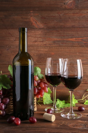 Wine bottle and glasses with grapes on wooden background