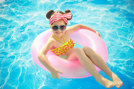 Little girl in swimming pool on sunny day Stock Photo