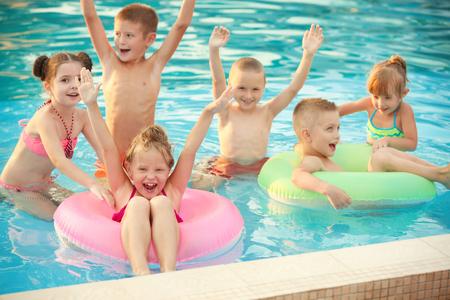 Bambini piccoli in piscina in giornata di sole
