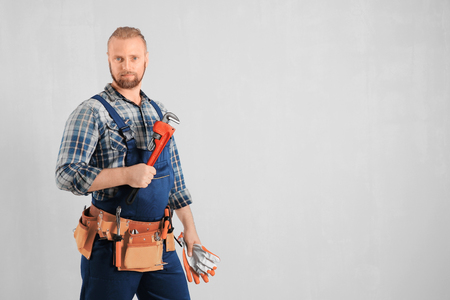 Handsome plumber with pipe wrench and gloves on light background