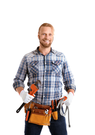 Handsome plumber with pipe wrench and flexible hose isolated on white Archivio Fotografico
