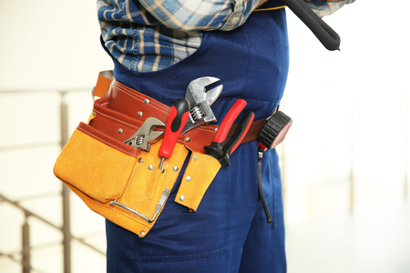 Worker with tools belt on light background, close up view