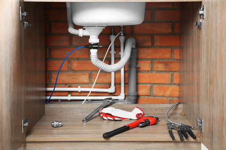 Plumber tools and gloves under sink, close up view