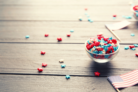 Sprinkles in glass bowl on wooden background