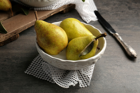 Green pears in plate on grey background