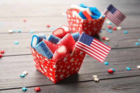 Delicious candies with USA flag in paper box on dark wooden background 免版税图像
