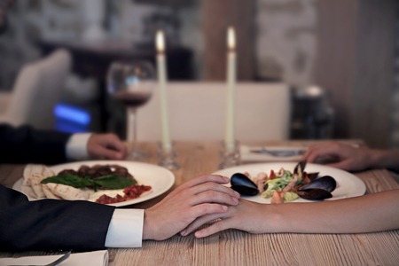 Man and woman holding hands together at restaurant, closeup Stock Photo