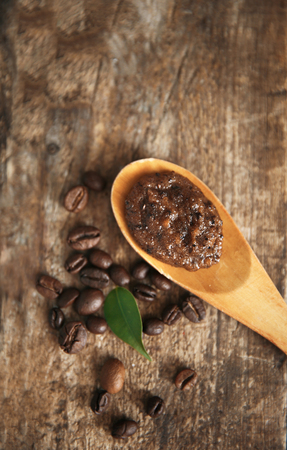 Coffee body scrub in spoon on wooden background